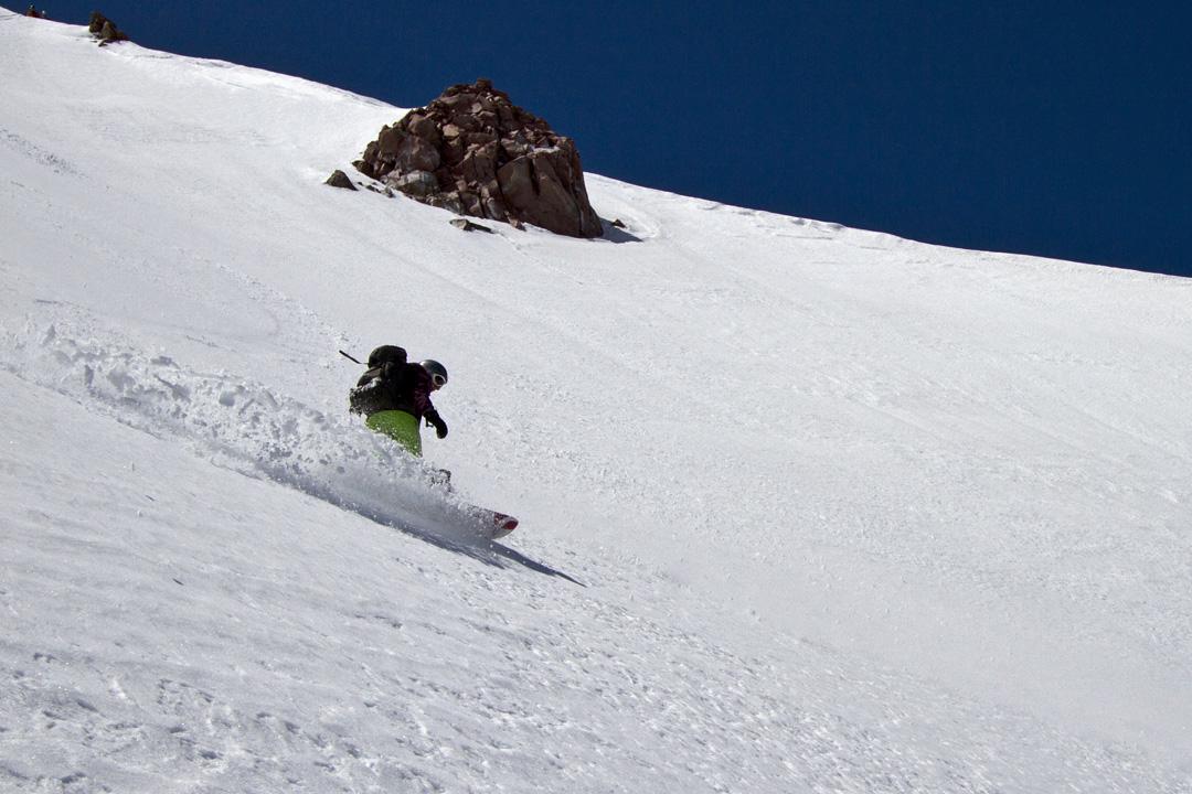 Allison Lightcap slashes her snowboard on Shastina