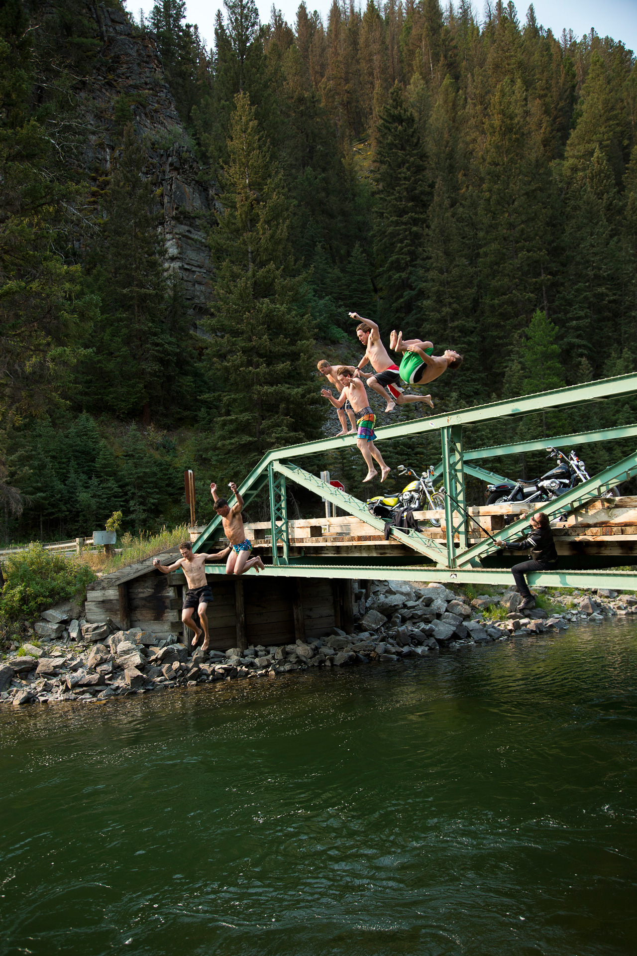 The team goes for an early morning bridge jump into the Galliton River in Montana