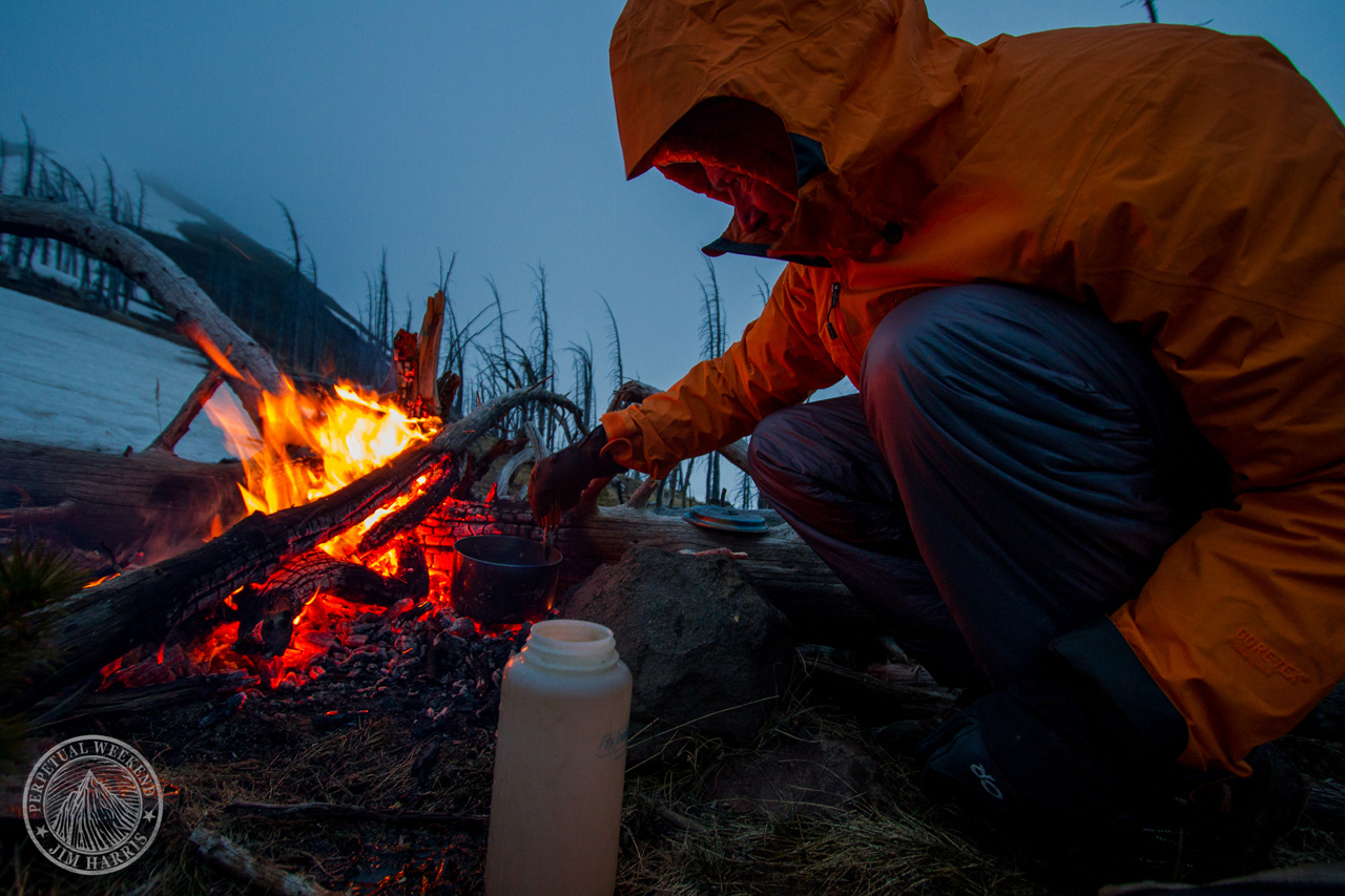 Forrest McCarthy melts water at a ridge line campsite as a storm rolls in. Photo by Jim Harris